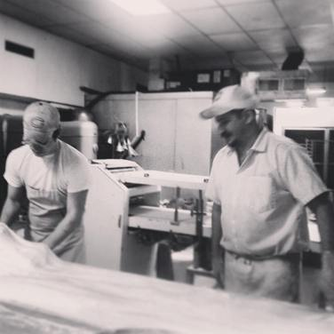 Steve teaching his son, Mike, how to roll cinnamon bread