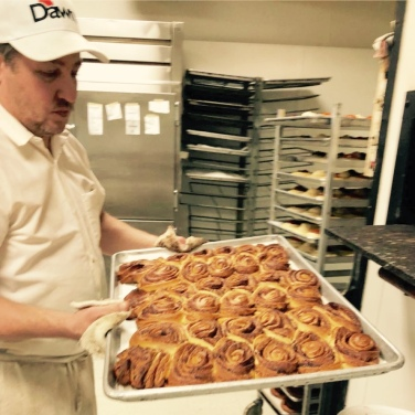 Steve pulling a tray of cinnamon coffee cakes out of the oven